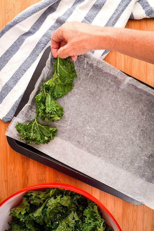 Kale chips being placed on a pan with parchment paper.