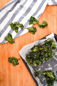 Kale chips scattered on a pan.