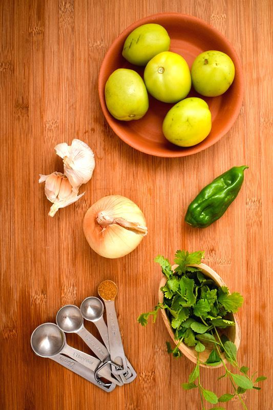 A bowl of tomatillos, serrano pepper, garlic, cilantro and spices laid out.