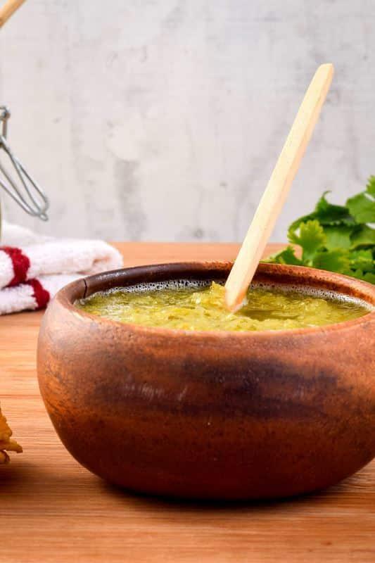 A wooden bowl of tomatillo salsa, cilantro in the background.