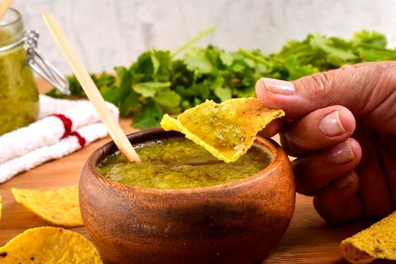 A wooden bowl of tomatillo salsa, a jar of tomatillo salsa, cilantro and tortilla chips in the background. Hand dipping a tortilla chip in the salsa.