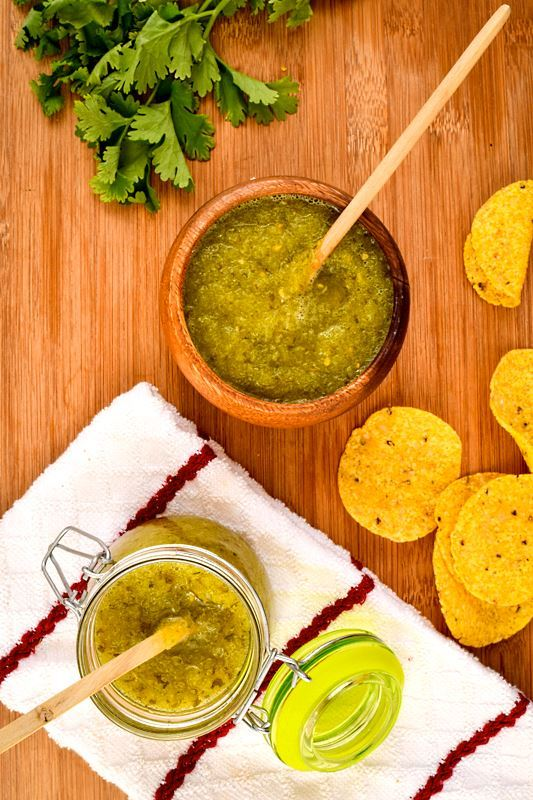 A wooden bowl of tomatillo salsa, a jar of tomatillo salsa, cilantro and tortilla chips in the background.