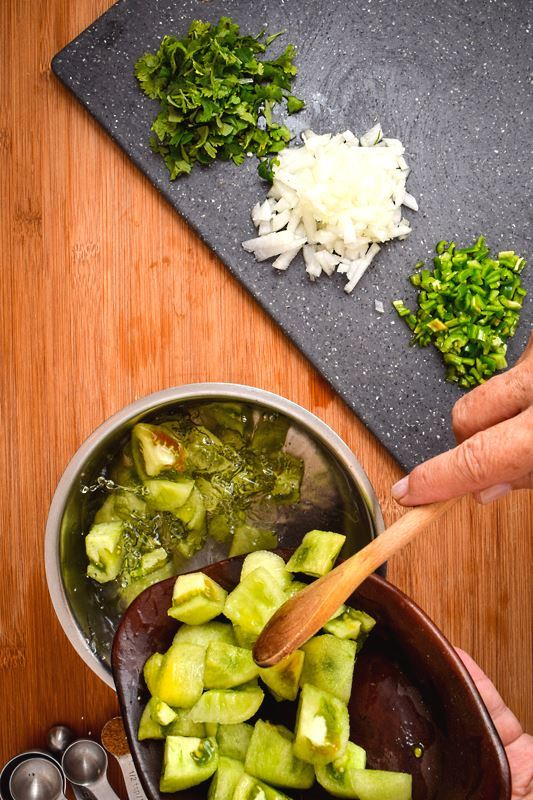 Hand adding tomatillos to pot of water, prepped ingredients on the side.