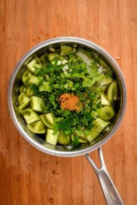 All tomatillo salsa ingredients in a pot of water.