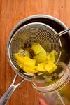 Cooked tomatillo salsa ingredients being transferred to a blender jar.