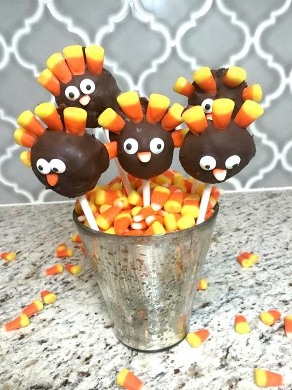 Turkey oreo cake pops in a small pail with candy corn.