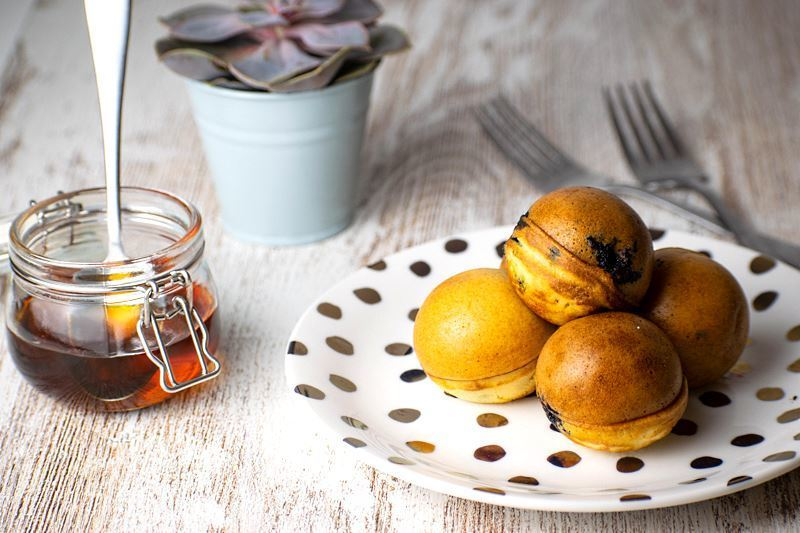 Pancake cake pops on a white plate with polka dots, a jar of maple syrup in the background.