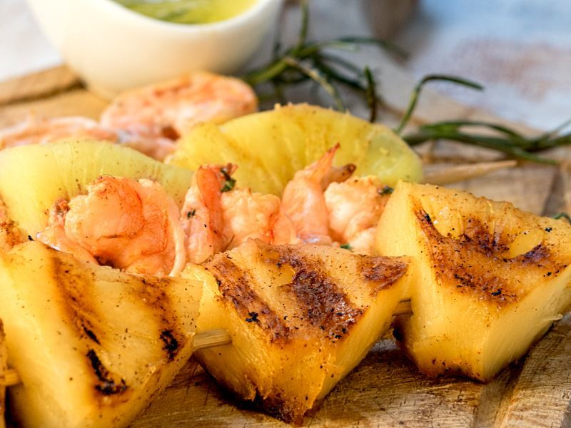 Shrimp on Rosemary Skewers with Rum-Soaked Pineapple wedges.