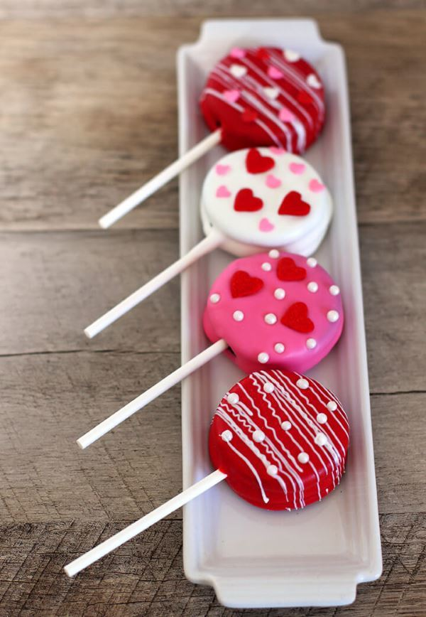 Oreo cake pops covered in red, white and pink icing, lined up on a porcelain dish.
