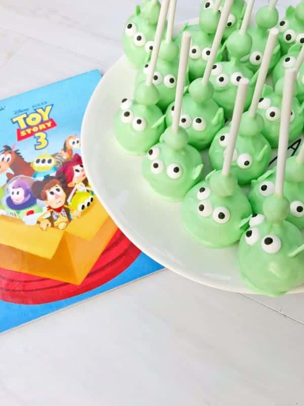 Alien cake pops on a plate, toy story napkin underneath.