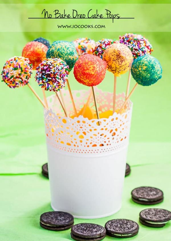 Colorful no bake oreo cake pops in a white stand.