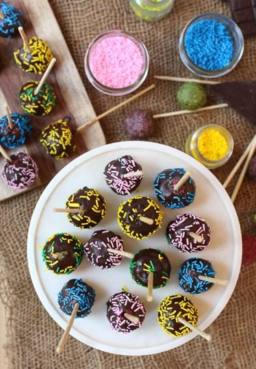 Rainbow cake pops with chocolate coating and colorful sprinkles on a tray.