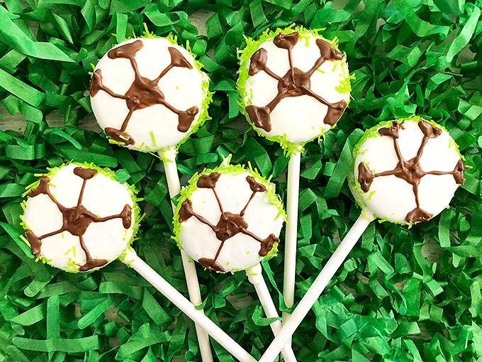Soccer oreo cake pops on green shredded paper.