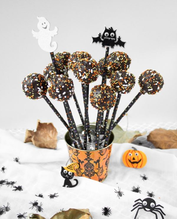 Halloween dark chocolate cake pops with sprinkles in a Halloween themed mini bucket.