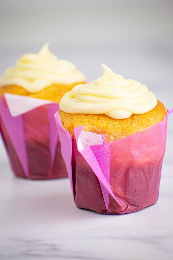 2 cupcakes with buttercream frosting in purple wrappers.