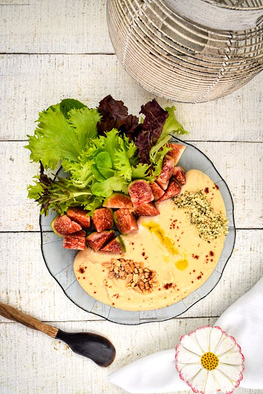 Hummus bowl with fresh figs, greens, nuts, hemp seeds and olive oil on a wooden background. Napkin with a fabric flower and small spatula on the side.