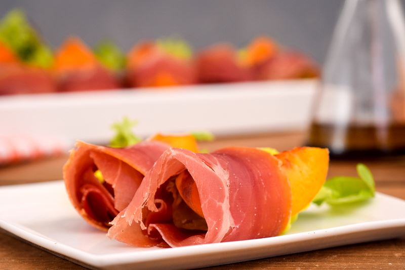 Grilled Peaches Wrapped in Proscuitto on a porcelain appetizer plate, balsamic dressing in the background.