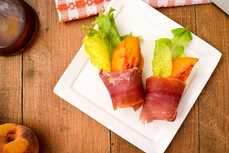 Grilled Peaches Wrapped in Proscuitto on a porcelain appetizer plate, balsamic dressing and peaches in the background.