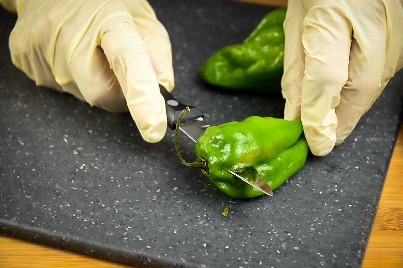 Slicing jalapeno peppers in half on a cutting board with rubber gloves.