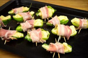 Raw jalapeno poppers on a baking sheet.
