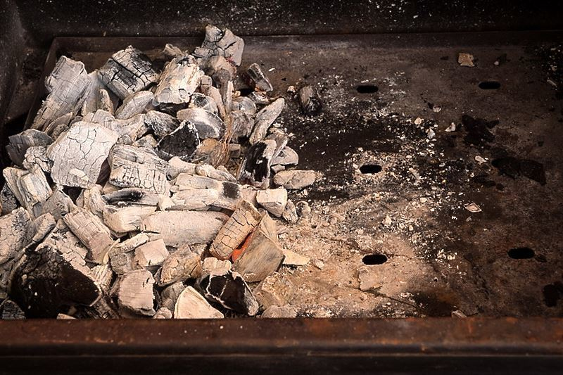 Charcoal grill with coals on one side.