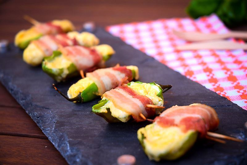Grilled jalapeno poppers on a black rectangular serving tray.