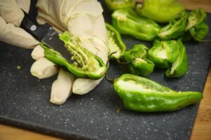 Removing the seeds from a jalapeno pepper sliced in half on a cutting board with a rubber glove.