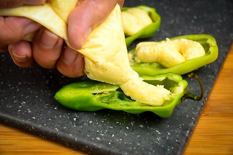 Adding cheese through a piping bag into a jalapeno pepper slice.