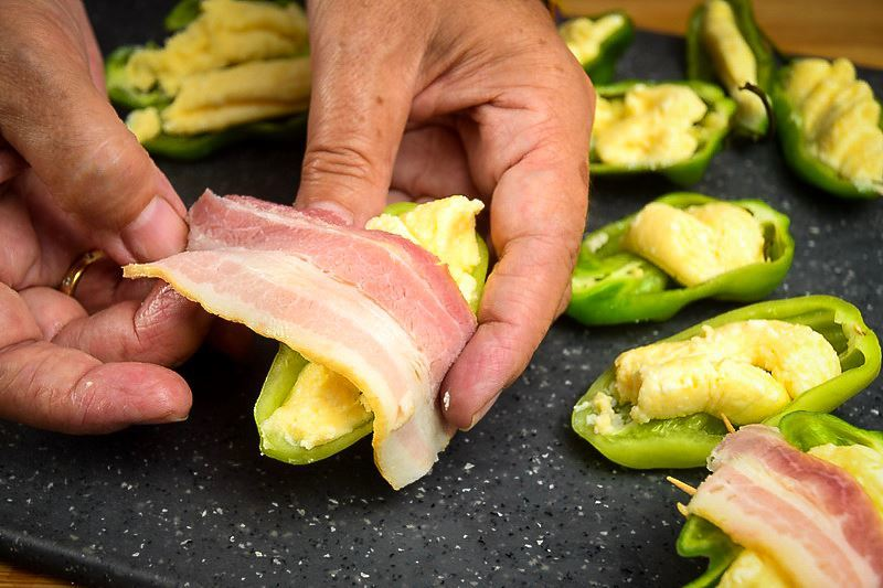 A hand wrapping a jalapeno popper with raw bacon on a cutting board.
