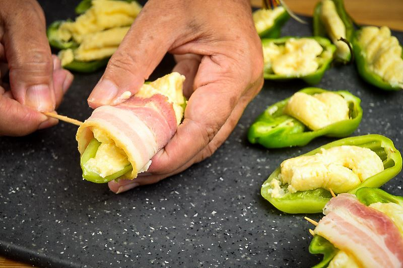 A hand piercing a jalapeno popper with a toothpick, on a cutting board.
