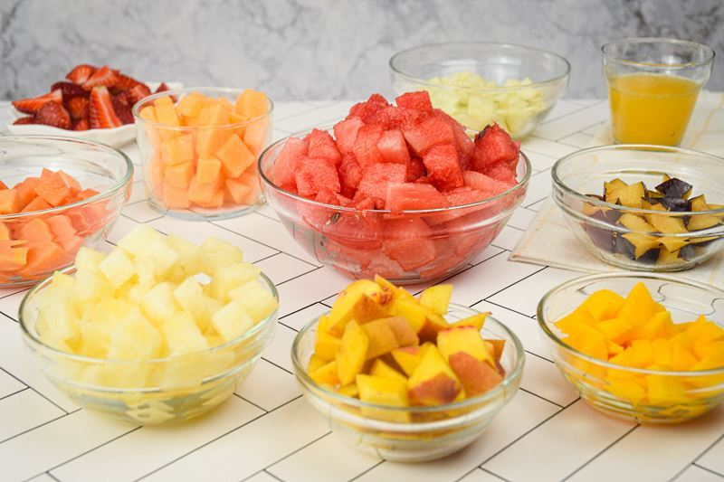 Prepped fruit salad ingredients in bowls.