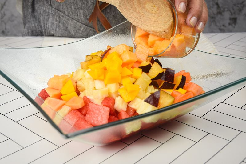 Chopped cantaloupe being added to bowl of fruit salad.