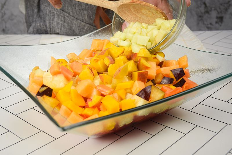 Chopped apple being added to bowl of fruit salad.