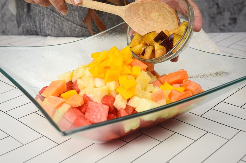 Chopped plum being added to bowl of fruit salad.