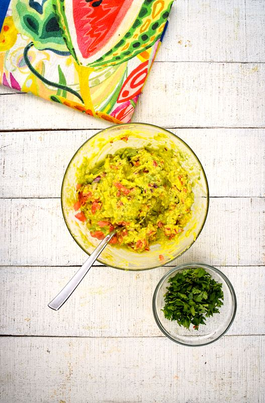 A bowl of guacamole, cilantro and colorful napkin on the side, white wood background.