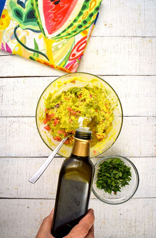 A bowl of guacamole, cilantro and colorful napkin on the side, white wood background. A hand adding olive oil to the bowl.