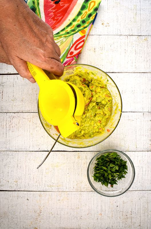 A bowl of guacamole, cilantro and colorful napkin on the side, white wood background. A hand adding lemon juice to the bowl.