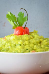A bowl of guacamole with cilantro and a pepper.