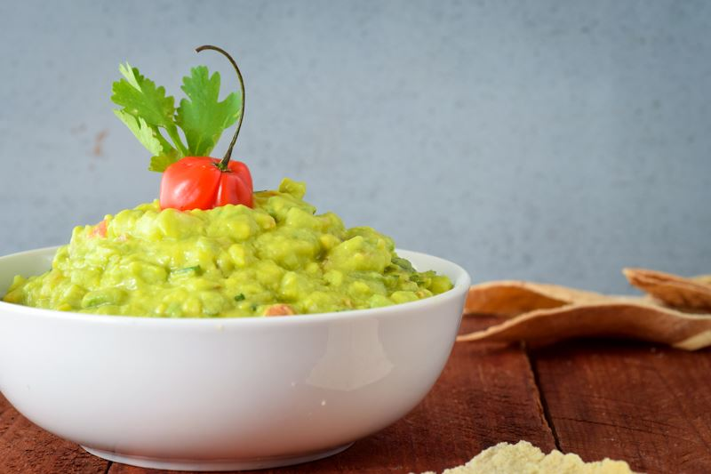 A bowl of guacamole with cilantro and a pepper. Dark reddish-brown background.