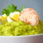 A bowl of guacamole with sliced quail eggs and prawns.