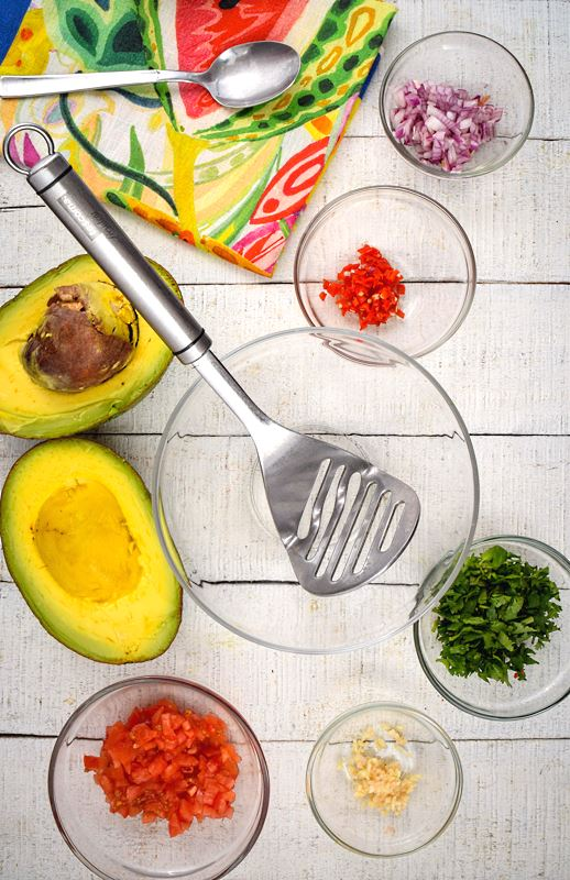 An opened avocado, prepped tomatoes, red onion, serrano peppers, cilantro and a colorful napkin on white wood background.