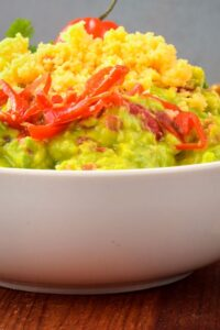 A bowl of guacamole with a chili pepper, cilantro, Mexican seasoning and cheddar cheese.