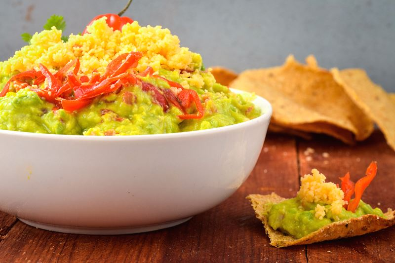 A bowl of guacamole with a chili pepper, cilantro, Mexican seasoning and cheddar cheese. tortilla chips on the side.