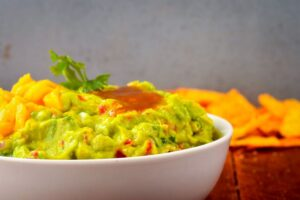 A bowl of guacamole with mango and passion fruit coulis.