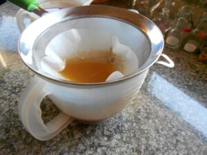 Maple syrup filtering into a measuring cup.