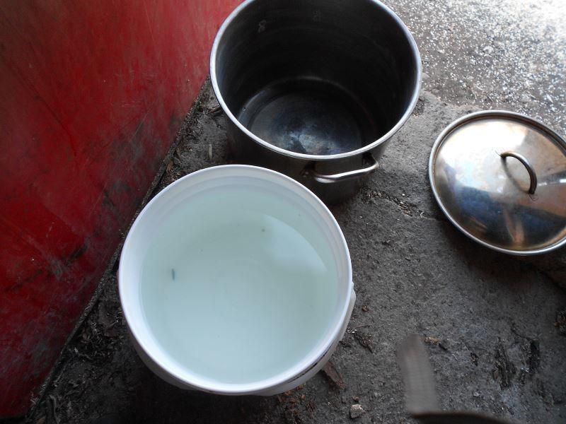 A pail and a large pot on concrete floor.