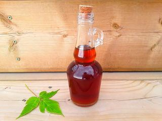 Maple syrup in a glass bottle with a maple leaf on the side, wood background.