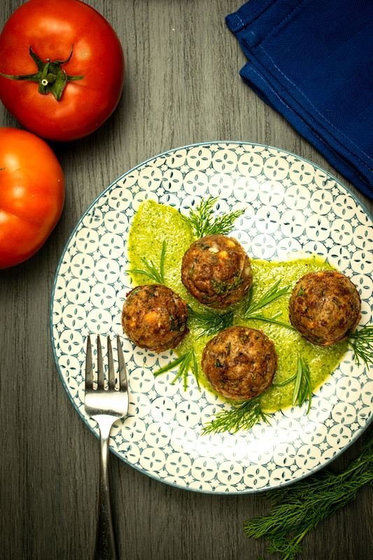 Mediterranean meatballs on a plate with pesto, tomatoes and blue cloth napkin on the side, grey wood background.