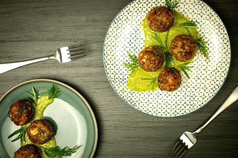 Mediterranean meatballs on a plate with pesto, grey wood background.