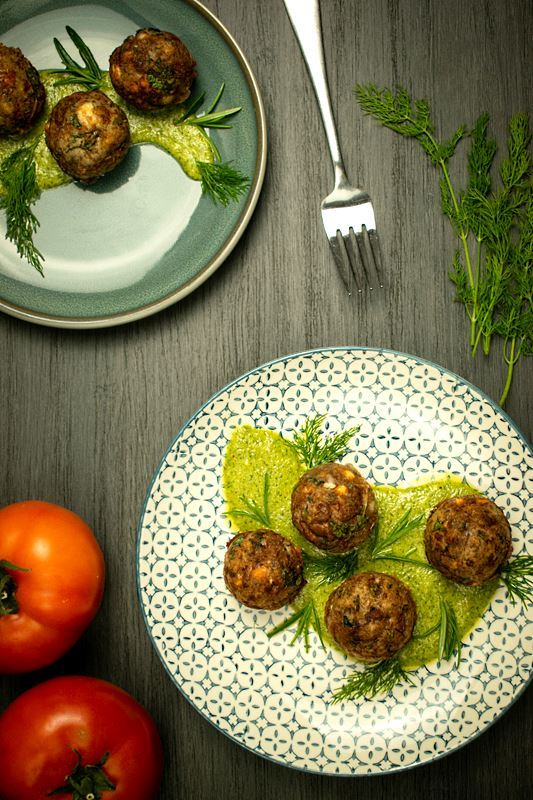 Mediterranean meatballs on a plate with pesto, tomatoes and dill on the side, grey wood background.